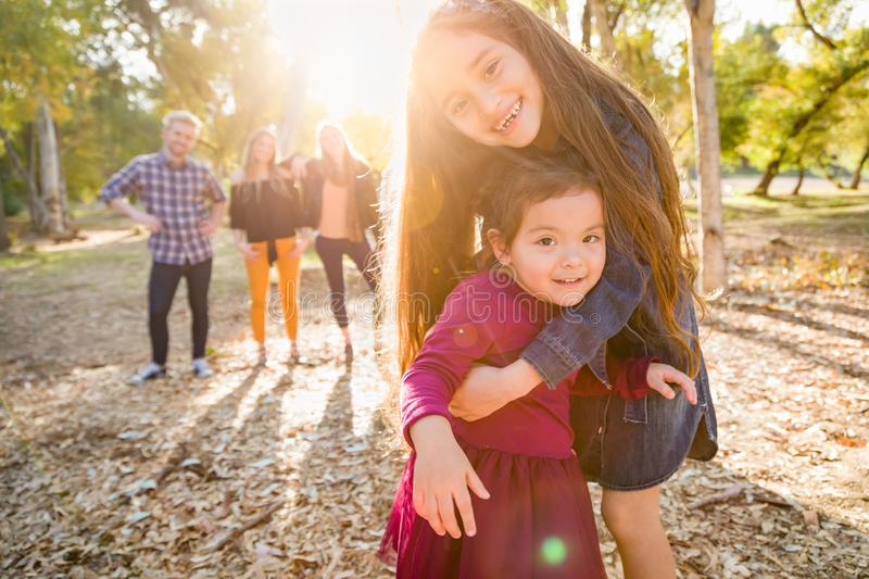 Happy Mixed Race Young Girl Sisters Outdoors with Family Behind stock photo