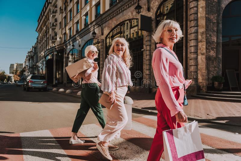 Happy modern grandmothers are crossing crosswalk together stock photos