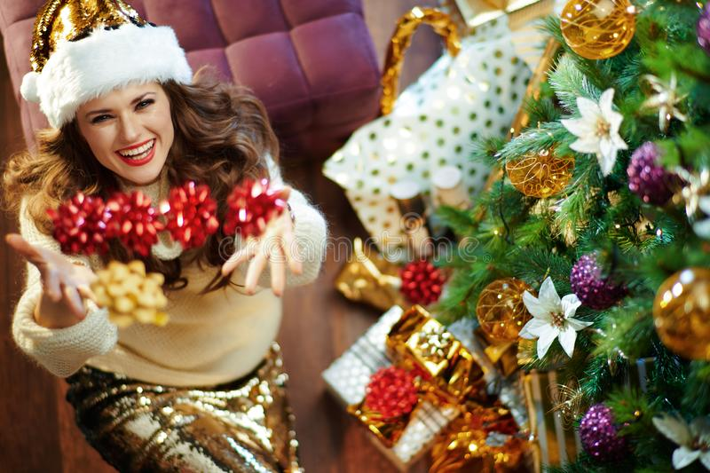 Happy modern middle age woman throwing red bows up stock images