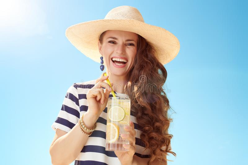 Happy modern woman against blue sky with refreshing cocktail royalty free stock images