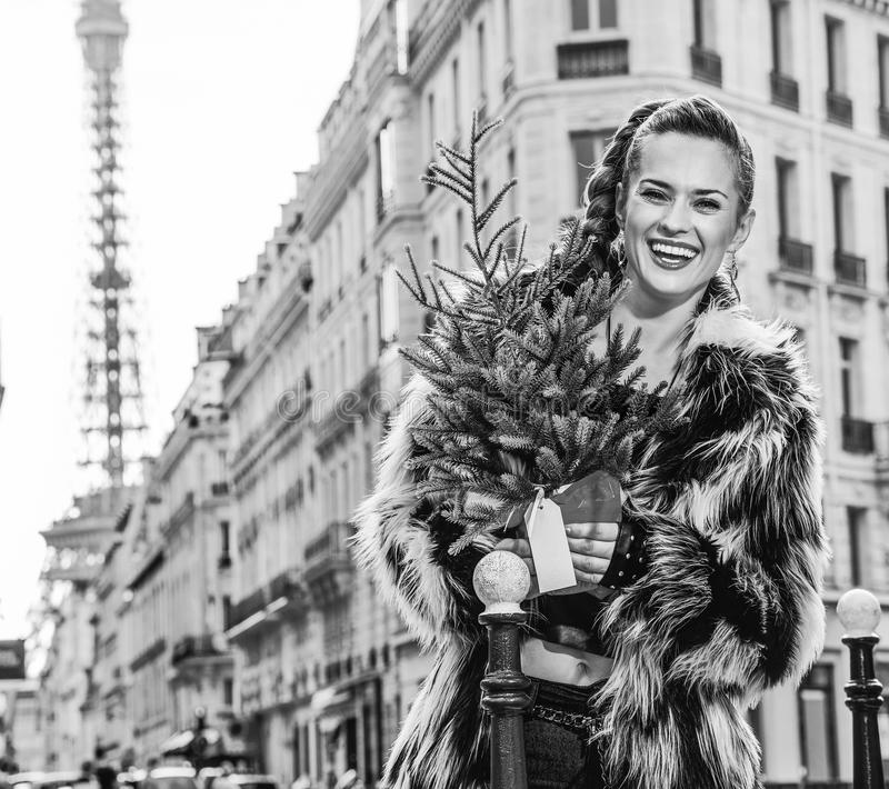 Happy modern woman with Christmas tree in Paris, France. Boiling hot trendy winter in Paris. Portrait of happy modern woman with Christmas tree in Paris, France stock image