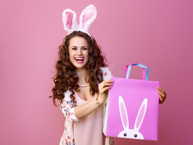 Happy modern woman on pink showing Easter shopping bag royalty free stock photography