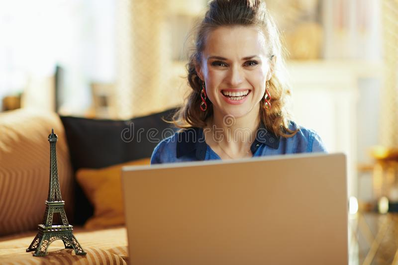 Happy modern woman with souvenir of eiffel tower using laptop royalty free stock images
