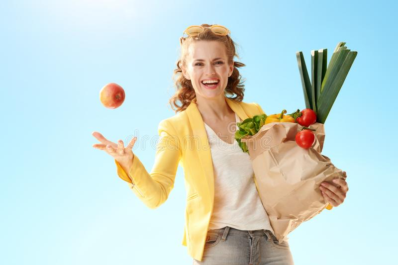 Woman with paper bag with groceries throwing apple up agai. Happy modern woman in yellow jacket with paper bag with groceries throwing an apple up against blue stock images