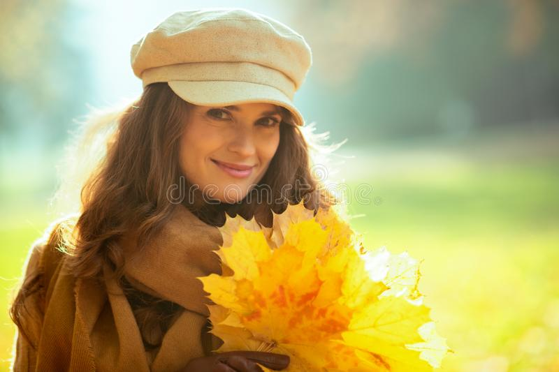 Happy modern woman with yellow leaves outside in autumn park royalty free stock photo