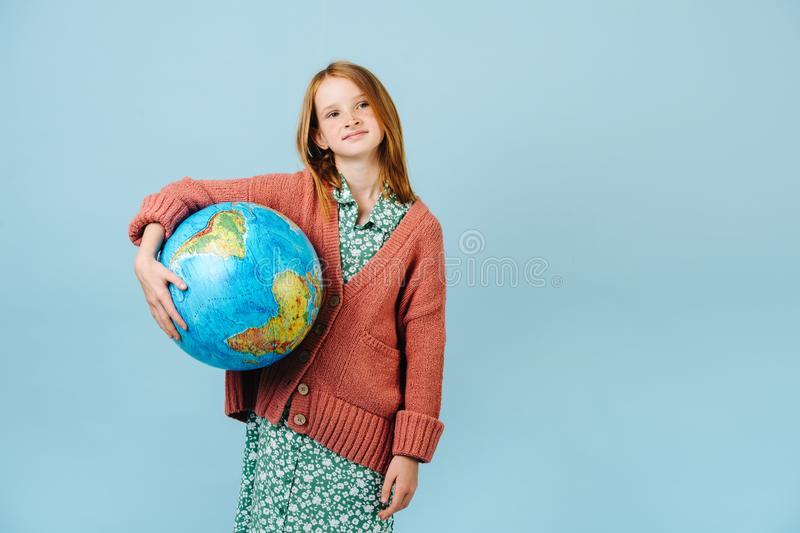 Teenage girl holding planet earth globe under her arm stock photos