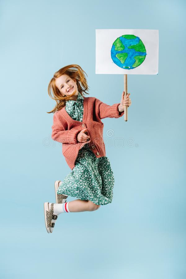 Teenage girl holding planet earth sign jumping in support of zero waste movement stock photos