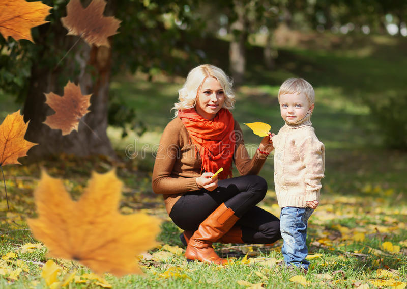 Happy mom and child playing together in warm autumn day stock images