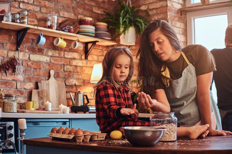 Happy mom cooking with her little daughter in loft style kitchen at morning. Family concept. Happy mom cooking with her little daughter in loft style kitchen at royalty free stock images