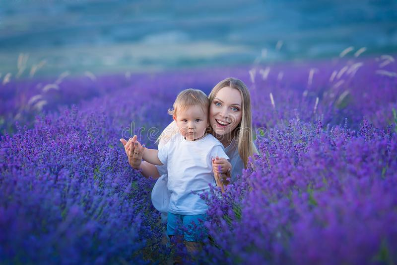 Happy mom with cute son on lavender background. Beautiful woman and boy in meadow field. Lavender landscape with lady and kid stock image