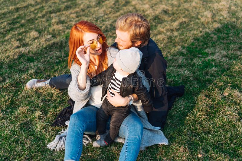 Happy mom dad and son hugging in the park royalty free stock photos