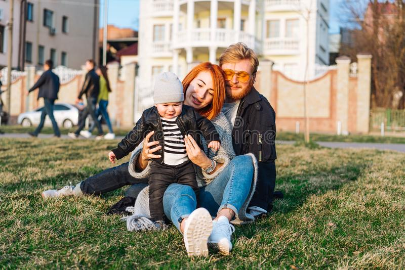 Happy mom dad and son hugging in the park stock photography