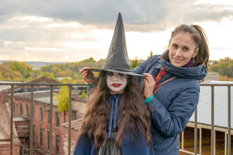 Happy mom and daughter get ready for halloween. cute witch with long curly hair posing in the photo next to her mother. Happy royalty free stock images