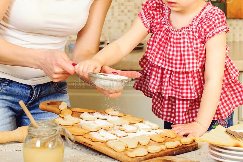 Happy mom and daughter are preparing cookies together. Homemade easter cookies. Happy family holidays. Little helper at kitchen. royalty free stock photo