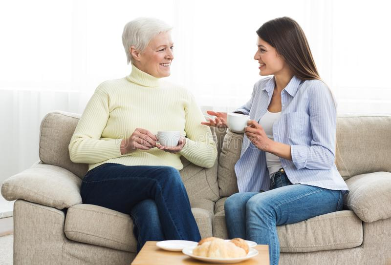 Happy mom and daughter talking and drinking tea royalty free stock photos