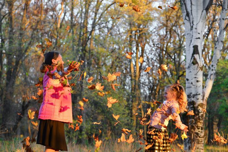 Happy mom and daughter throw autumn leaves up in the park, joyful family royalty free stock image