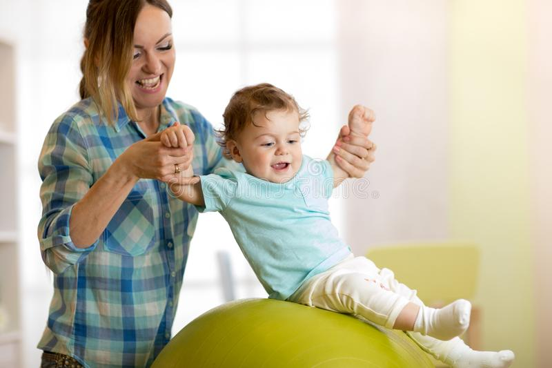 Happy mother and baby boy on fitness ball at home. Gimnastics for kids on fitball. royalty free stock photo