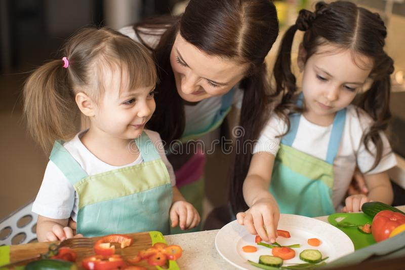 Happy mom and her kids daughters enjoy making healthy meal together at their kitchen stock photos