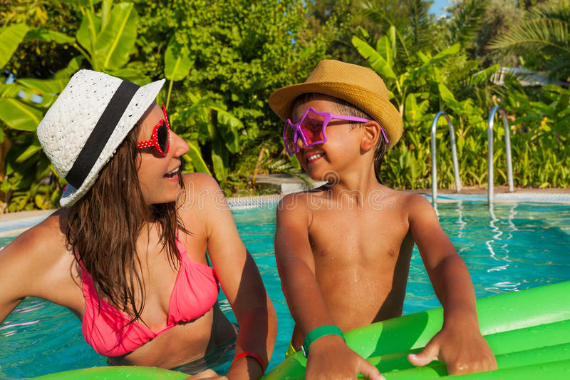 Happy mom and her son wearing sunglasses in pool. Happy mom and her son wearing sunglasses and hats in the swimming pool outside in summer stock photos