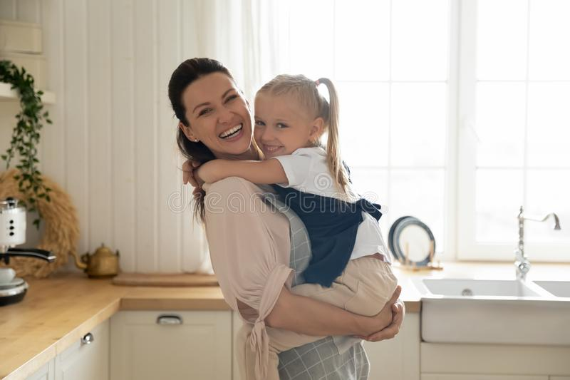 Happy mom housewife hold little child daughter in kitchen, portrait royalty free stock images