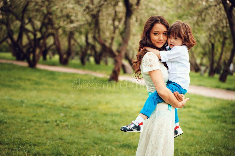 Happy mom hugs and kiss toddler kid son outdoor in spring or summer royalty free stock photo