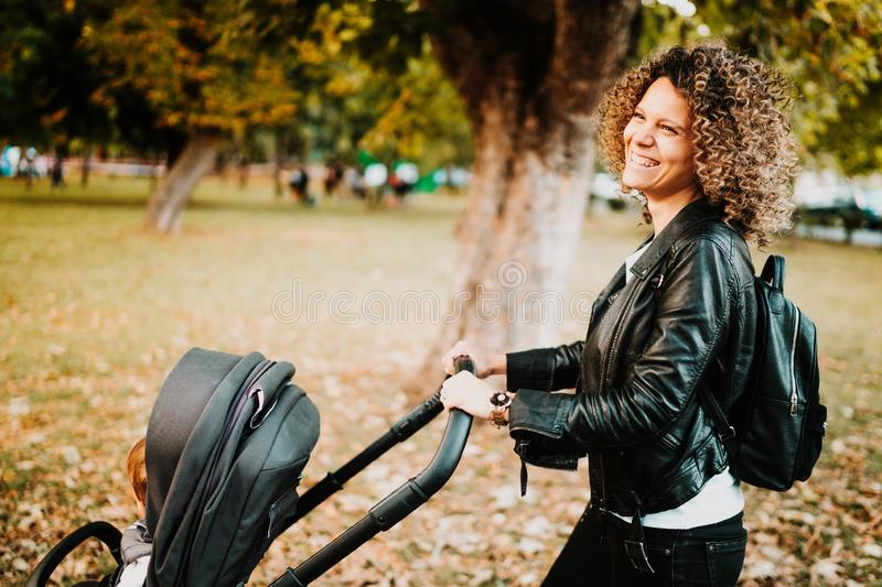mom pushing stroller and smiling, laughing. Mother walking with baby stroller royalty free stock photo