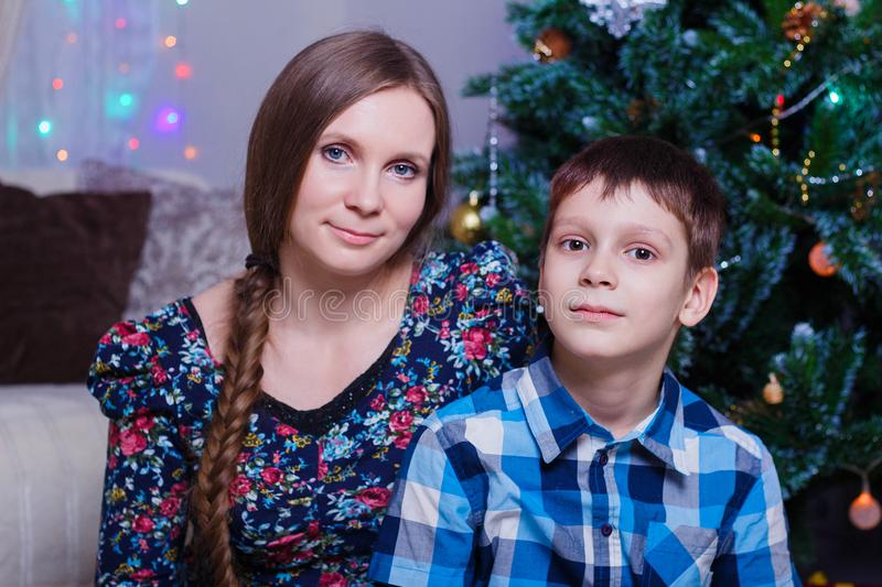 Happy mom and son at home celebrate Christmas, New year mood, Christmas tree and gifts.  royalty free stock image