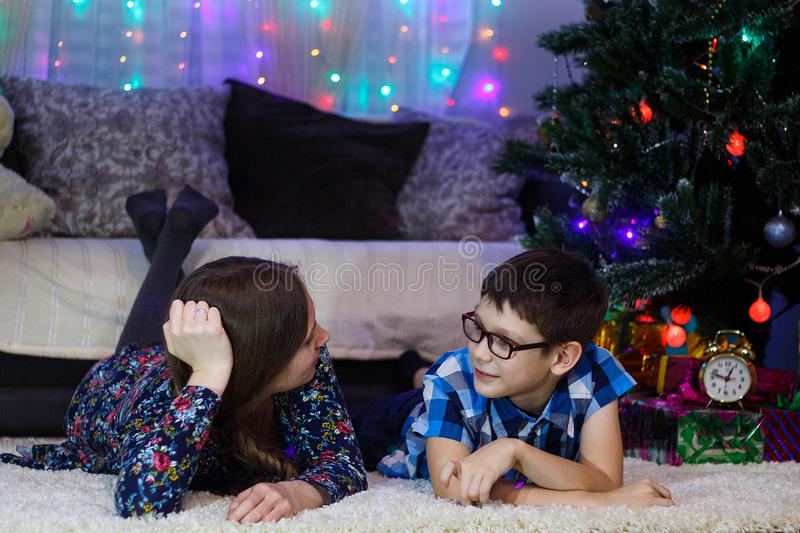 Happy mom and son at home celebrate Christmas, New year mood, Christmas tree and gifts.  stock photo