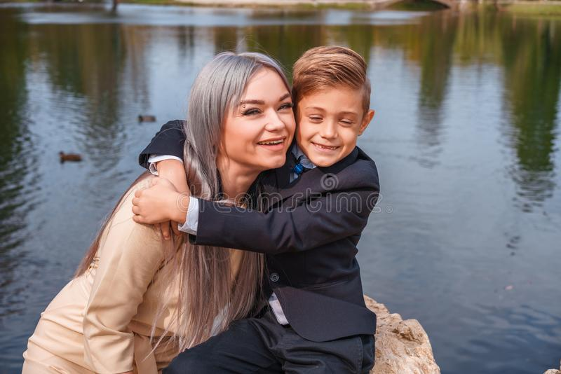 Happy mom and son hugging outdoors by the lake stock image