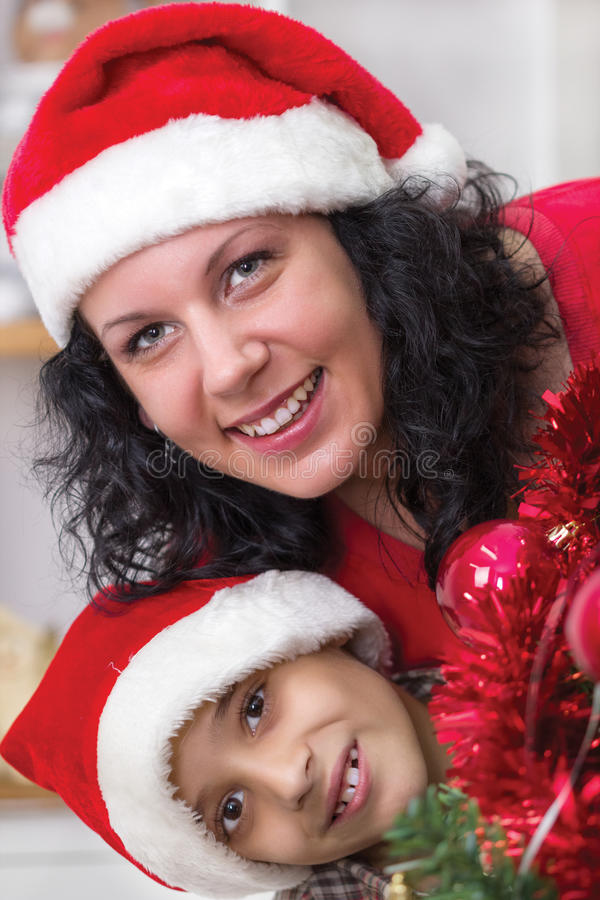 Happy mom and son next to the Christmas tree royalty free stock image