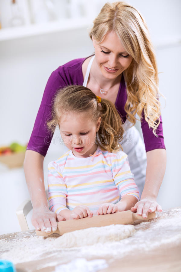 Happy Mom teaches daughter how to use a rolling pin stock photos