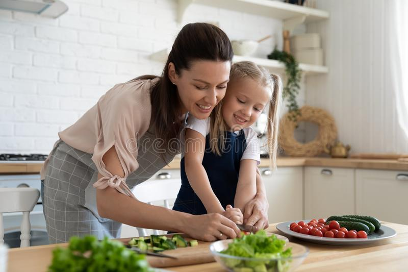 Happy mom teaching preschool daughter cutting salad in kitchen interior stock photography