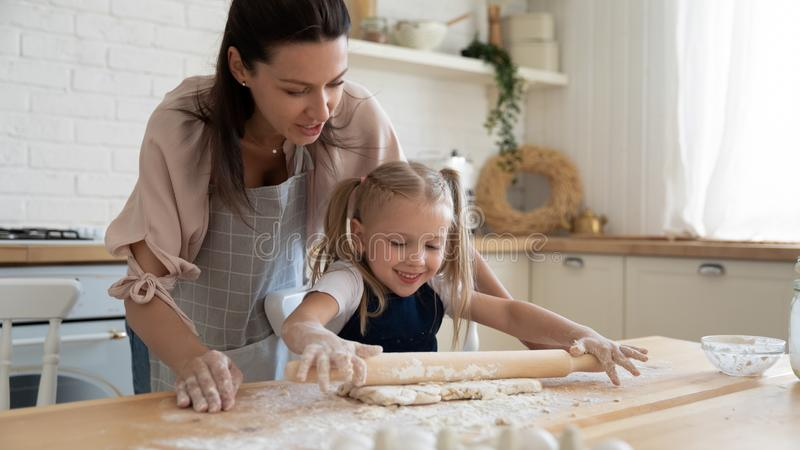 Happy mom teaching small child daughter rolling dough in kitchen stock photography
