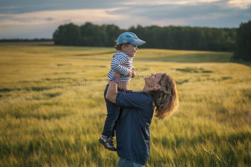 Happy mom throws her son up in her arms royalty free stock images