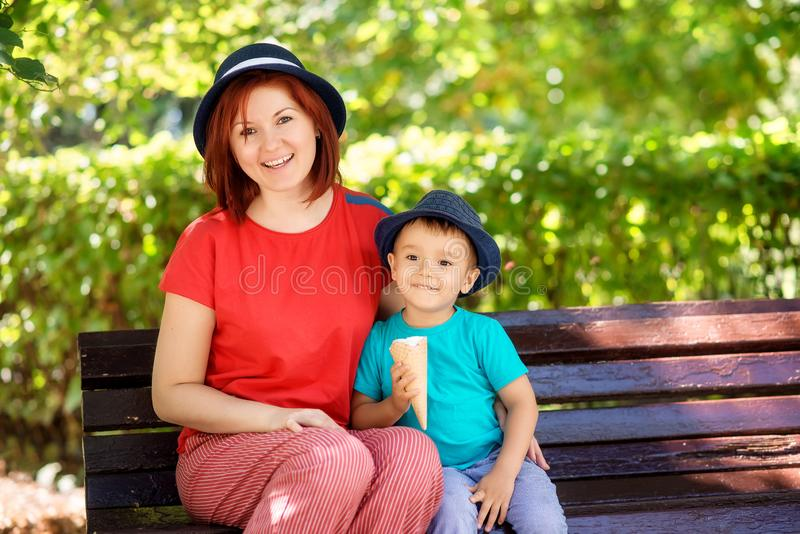 Happy mom and toddler child in blue hats sit on brown wooden bench in park, kid is holding ice-cream royalty free stock photo