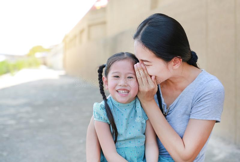 Happy mom whispering a something secret to her little daughter ear. Mother and kid communication concept royalty free stock images