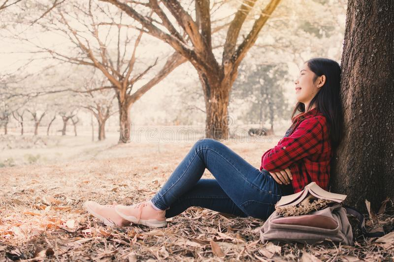 Happy moment hipster woman relaxing and sitting under the big tree on park stock photography