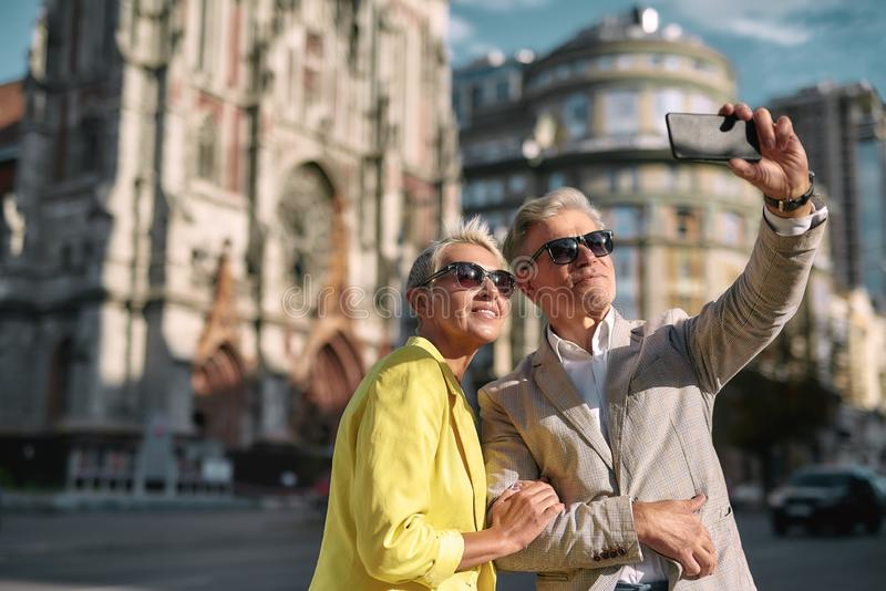 Happy moments. Beautiful mature caucasian couple in sunglasses taking selfie by mobile phone while spending time stock images