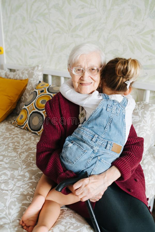 Happy moments. Little girl with her great grandma spending quality time together royalty free stock photography