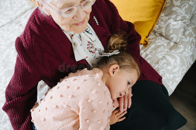 Happy moments. Little girl with her great grandma spending quality time together stock image