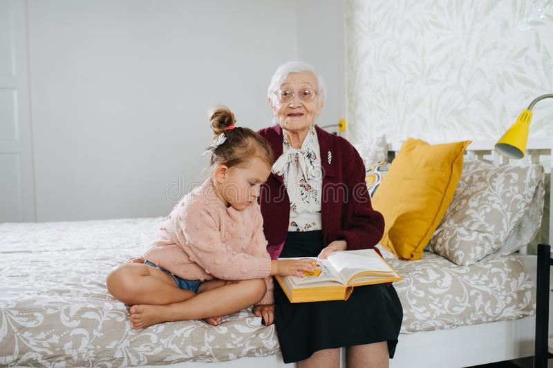 Happy moments. Little girl with her great grandma spending quality time together stock photo