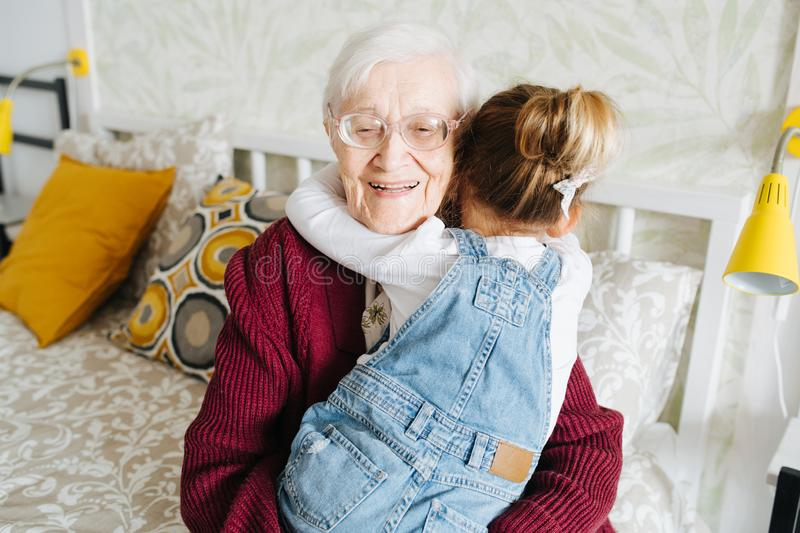 Happy moments. Little girl with her great grandma spending quality time together stock images