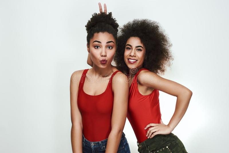 Happy moments. Two cute afro american women in jeans shorts are gesturing and making a face while standing against grey stock photography