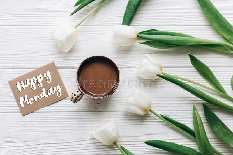 Happy monday text sign on greeting card with tulips and morning. Coffee on white wooden rustic background with space for text. stylish flat lay with flowers and royalty free stock photos