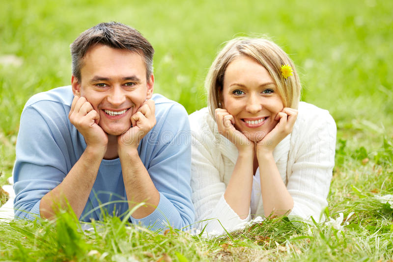 Happy mood. Portrait of happy couple looking at camera while lying on green grass stock photos