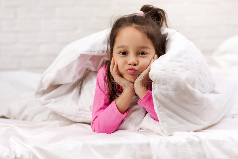 Happy morning baby in bed. Child dabbles in bed stock image
