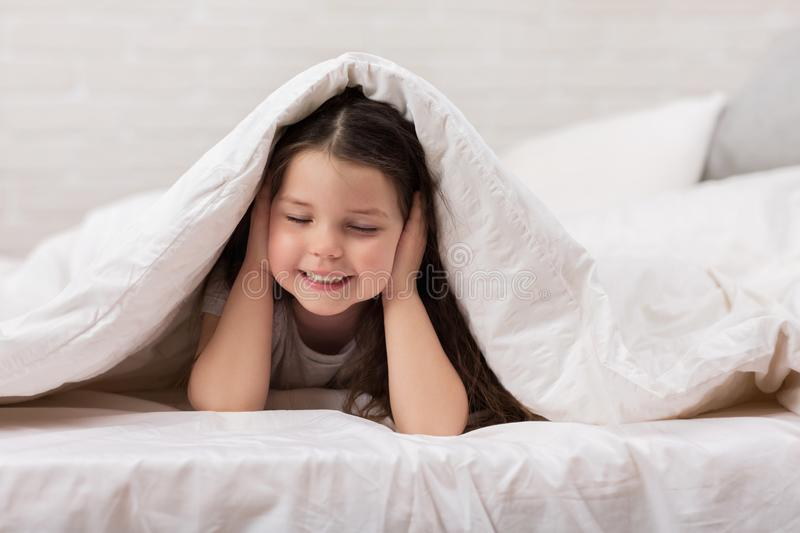 Happy morning baby in bed. Child dabbles in bed. child covers his ears royalty free stock image