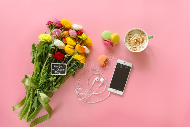 Happy Mother`s Day note on the buttercup flowers, cup of cappuccino, makarons cake and mobile with headphones on the pink backgro stock images