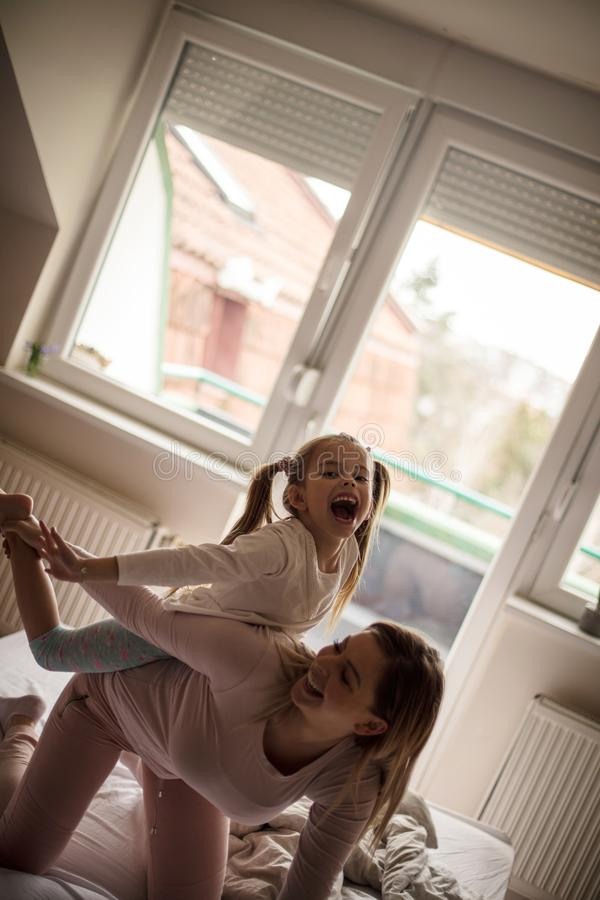 Happy morning. Mother and daughter playing on bed royalty free stock photo