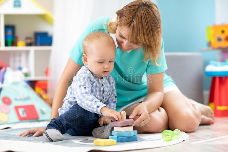 Happy mother and adorable baby boy playing on floor mat in sunny nursery room. Cute child with carer in creche royalty free stock photography